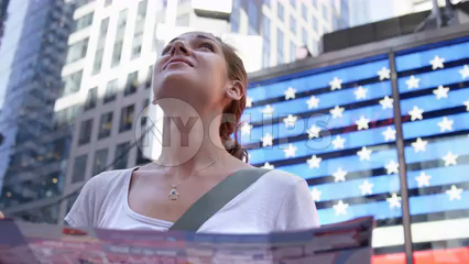 beautiful woman tourist looking around Times Square and at map in front of American flag LED - slow motion 4K in Manhattan NYC