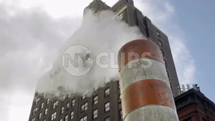 orange and white striped construction site pipe with steam - smoke coming from stack in NYC