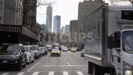 6th Ave traffic in Manhattan, Freedom Tower skyscraper in view with cars and taxicab driving in NYC
