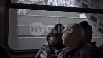 old couple looking out window from elevated subway train in winter, NYC