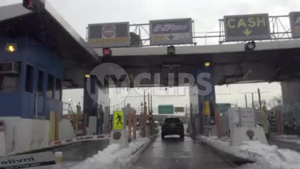 car driving pov entering e-z pass toll on highway snow in winter NYC
