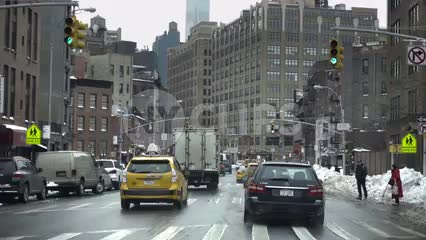 driving on Varick Street in winter - snow on 7th avenue with cars in traffic and Freedom Tower in background in Downtown Manhattan NYC
