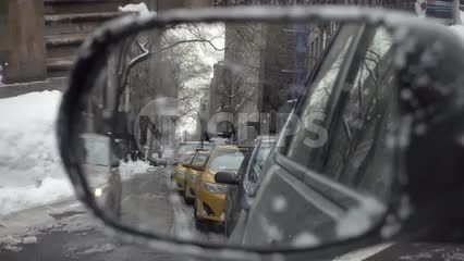 taxi cabs and cars in driver's side mirror while driving in slow motion on winter day with snow on ground in NYC