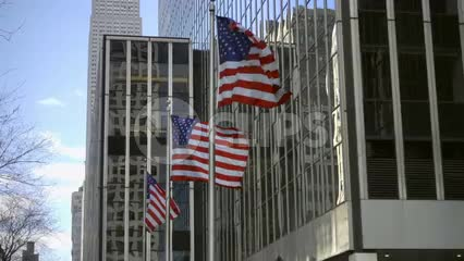 3 American flags waving in front of corporate buildings in Midtown Manhattan NYC