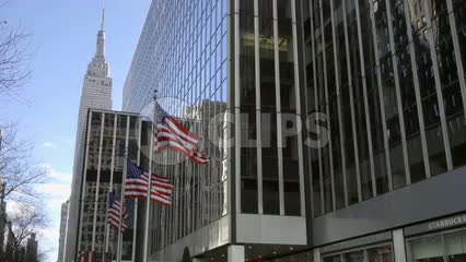 American flags waving on 34th street outside corporate office building with Empire State Building landmark in background, Manhattan NYC 1080 HD