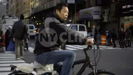 man on bicycle riding in street on fall day in Manhattan NYC - slow motion