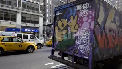 beautiful colorful graffiti truck parked on 7th Ave in Manhattan outside FIT on fall day in slow motion NYC