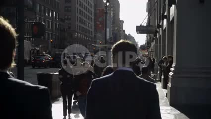 men in suits walking in slow motion on Park Ave in Midtown Manhattan on bright sunny day in NYC