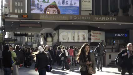 Madison Square Garden on bright sunny fall day - people walking outside in slow motion - woman on headphones in NYC