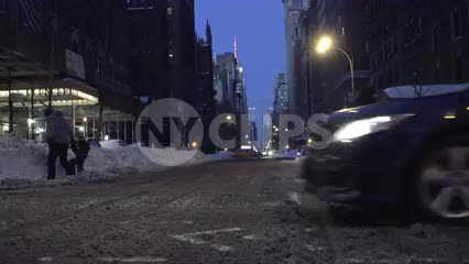 Lower 5th Ave in winter at night - low view of slush on street - snow on ground with cars and taxi cab driving by in NYC