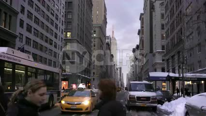 people crossing 5th ave in early evening winter day, Empire State Building and taxi in background, 1080 HD in NYC