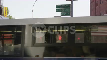 125th Street sign in Harlem with bus passing on corner, uptown NYC