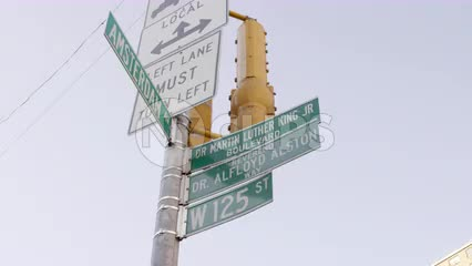 125th St and Amsterdam street sign tilting down to chicken and pizza store in Harlem NYC