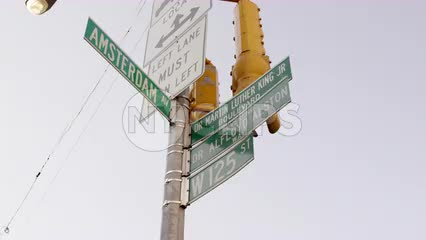 125th St and Amsterdam Ave sign tilting to Harlem housing projects uptown NYC