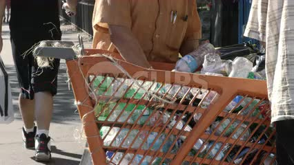 man collecting bottles in shopping cart uptown in gritty Harlem recycling station in 4K