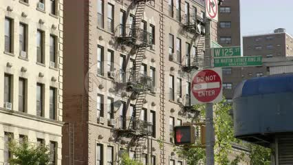 125th Street sign Martin Luther King Jr. Blvd do not enter signs tenements buildings with fire escapes in Harlem with cars driving by in 4K