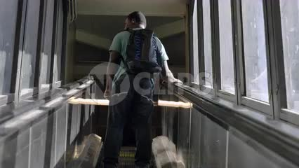 student with backpack - African American kid on escalator at 125th St subway station in Harlem