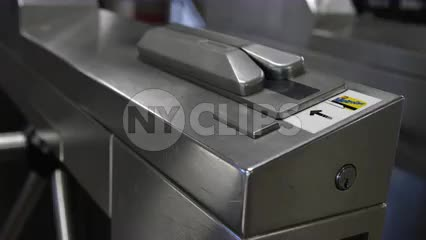 close-up of hand swiping Metro card in subway train station turnstile at 125th Street in Harlem