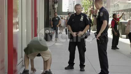 NYPD police officers and drunk homeless man getting up off street in Midtown Manhattan on summer day