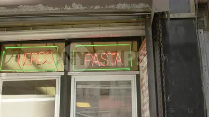 neon heros and pasta sign in pizzeria deli shop with cook in uniform in window