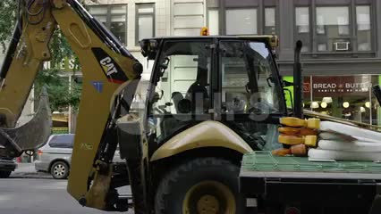 yellow construction shovel digger tractor driving down 5th Ave on sunny day in Manhattan NYC