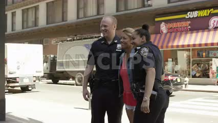 police officers posing with tourist woman while husband takes photo on summer day - 5th ave in Manhattan NYC
