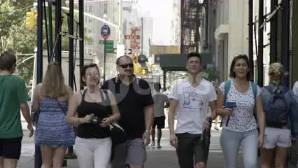 tourists walking down street on summer day in slow motion NYC