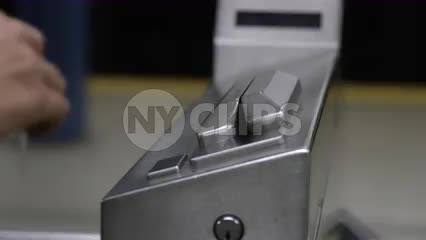 close-up on hand swiping Metro Card at turnstile in subway station in NYC