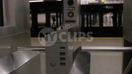 turnstiles in empty subway station and platform - tracking shot