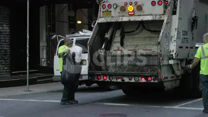 sanitation workers dumping trash in back of garbage truck in slow motion on summer day in SoHo Downtown Manhattan