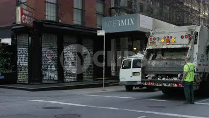 garbage truck on quiet empty street SoHo morning graffiti metal shutter gate over storefronts