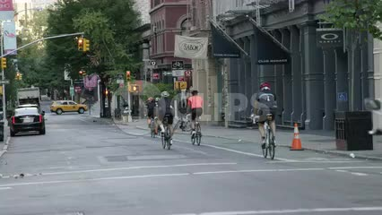 bicyclists riding in SoHo street on quiet summer morning in NYC
