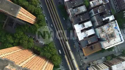 aerial of 1 train - subway riding on elevated track through Harlem with housing projects and rooftops in NYC