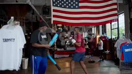 man training, boxing at Trinity Boxing Club in Financial District - boxer working out with trainer in gym with American flag