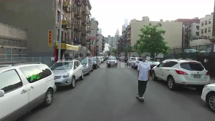 aerial of kid skating down Chinatown street rising to view of Manhattan skyscrapers