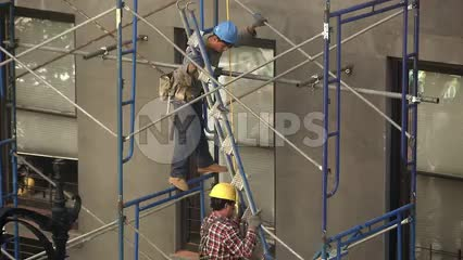 construction workers in hard hats carrying ladder climbing scaffolding on building