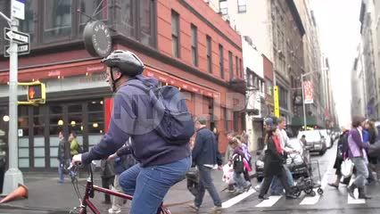 man on bicycle with helmet on fall day - 6th avenue in NYC
