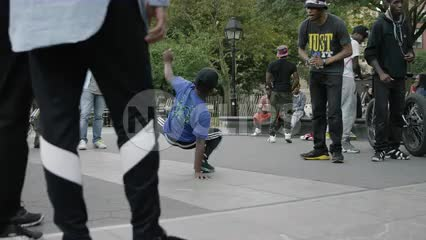B Boy doing head-spin in summer - breakdancing in Washington Square Park in NYC