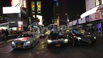 cars driving in slow motion through Times Square bright lights at night in Manhattan NYC