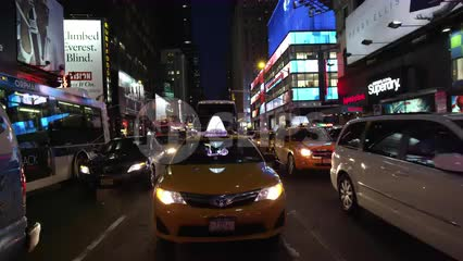 yellow taxi cab driving through Times Square at night in Manhattan