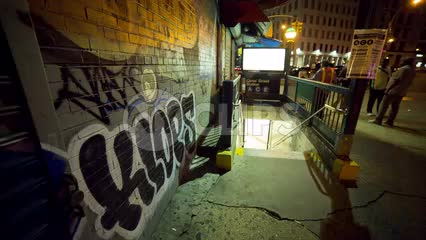 graffiti spray paint on wall outside A C E subway station with people walking up the stairs at night in Downtown Manhattan NYC