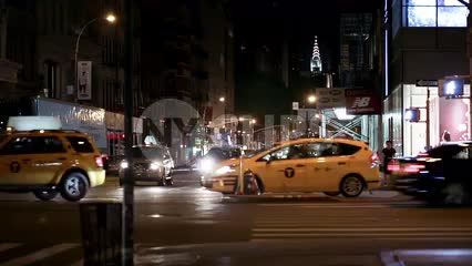 taxi cabs driving on Houston Street busy intersection with Chrysler Building in background at night downtown