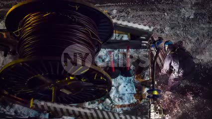 spool of fiber optic cables overhead view construction worker - man in hardhat working at night in street in winter snow - snowing