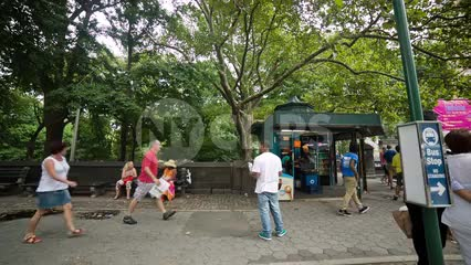 bus stop on Central Park West at Columbus Circle people walking man standing green summer trees