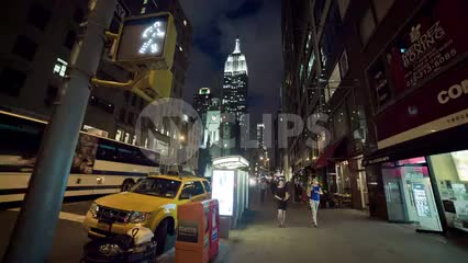 Empire State Building wide angle walk sign on 5th Ave at night in Manhattan