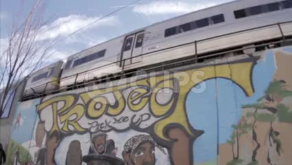 subway train on elevated track in Jamaica Queens graffiti wall spray paint hip hop mural