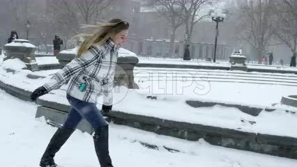 girl running in snow, blizzard in Washington Square Park snowing in winter storm slow motion 4K