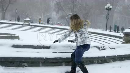 girl throwing snow up in air in Washington Square Park - having fun in winter blizzard snowstorm - snowing in slow motion