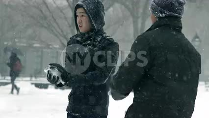 guys throwing snowballs in winter blizzard storm, snowing in Washington Square Park - snowball fight slow motion 4K