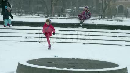 children running in slow motion - snow in Washington Square Park circle during winter blizzard - snowing in New York City NYC 4K and 1080 HD